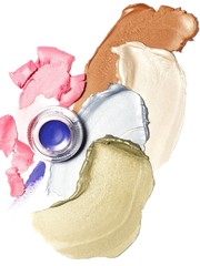 Overhead view of cosmetics bottle on smeared bronzer and pastel cream eyeshadow against white background