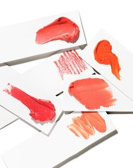 Shades of smeared red cosmetics against white background