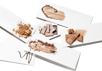 Crushed powdered bronzer and cosmetics against white background