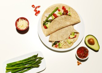 Tortilla wrap with avocado, cheese, rice, tomato salsa, and asparagus side dish