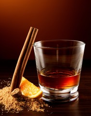 Glass of rum with cinnamon stick and orange slice table
