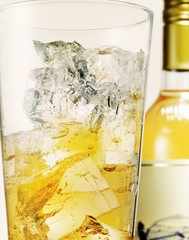 Close-up of alcohol with ice cubes in glass and bottle in background