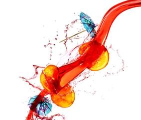 Orange slices splashing in bright liquid with blue paper drink umbrellas against white background