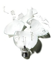 Close-up of broken glass lightbulb against white background