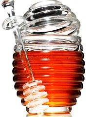 Close-up glass jar of honey with honey dipper against white background