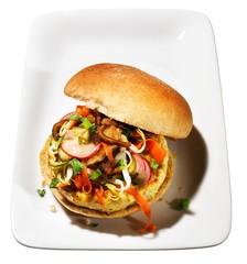 Egg burger bun with vegetable slices served plate