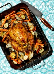 Cooked chicken with carrots and vegetables in pan