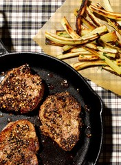 Cooked steak in cast iron skillet with fries