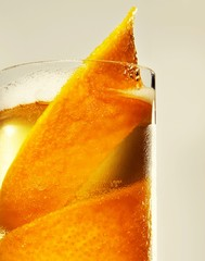 Close-up glass with alcohol drink and orange peel garnish
