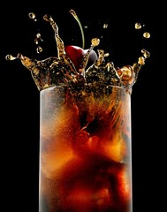 Low angle view of glass of alcohol with cherry splashing