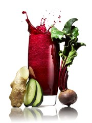 Glass of smoothie splashing with raw Beet, cucumber slices and ginger root