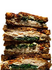 Stack of toasted turkey sandwiches with spinach