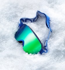 Ski goggles with bright green lens in snow