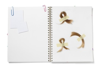 Baby book with hair taped onto blank page in spiral bound notebook