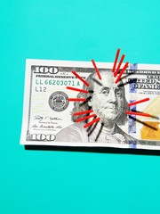 Acupuncture needlese hundred dollar bill against blue background
