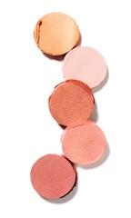 Circles of pink blush powdered cosmetics on white background