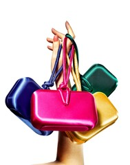 Woman's hand holding colorful purses