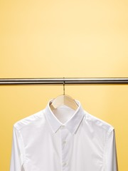 White shirt hanging hanger against yellow background