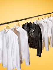 White button-down shirts and black leather jacket on hangers