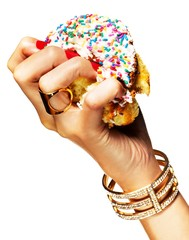 Woman's hand crushing donut with colorful sprinkles
