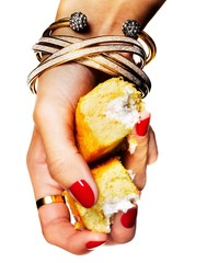 Woman's hand with bracelets crushing piece of yellow cake with cream filling