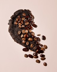 Coffee beans and brown exfoliating skin scrub pink background