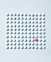 Pattern of white pills and one pink pill studio shot