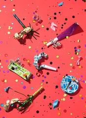 Party noisemakers and confetti against red background