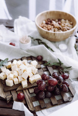 A beautifully served table with grapes, cheese, nuts and greens on a tree and napkins in rustic style
