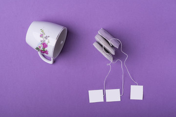 Decorated porcelain white cup with three tea bags on purple background. top view studio shot