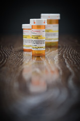 Variety of Non-Proprietary Prescription Medicine Bottles on Reflective Wooden Surface.
