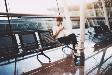 Young lovely Brazilian woman sitting alone in waiting room of modern airport terminal with tickets in one hand, smartphone in another hand, backpack near her on black metal seat; huge windows behind