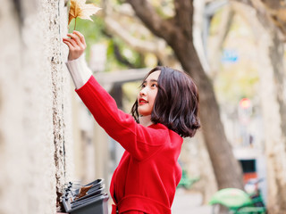 Beautiful young brunette woman wearing a red coat in autumn city. Outdoor fashion portrait of glamour young Chinese cheerful stylish lady in street. Emotions, people, beauty and lifestyle concept.