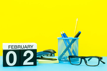 February 2nd. Day 2 of february month, calendar on yellow background with office supplies. Winter time