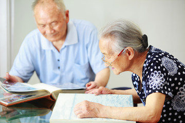 senior asian couple reading in home