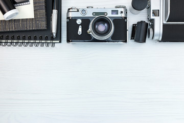 retro photo cameras, frame, notebook, pen, negative films on white wooden background flat view