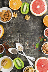 Ingredients of healthy dietary food breakfast pink grapefruit, orange, chia seeds, quinoa, green herbs, kiwi, wild rice, almonds, walnuts, hazelnuts on a gray background. The concept of natural