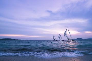 trois voiliers naviguent au coucher du soleil