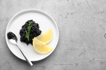 Plate with black caviar and slices of lemon on table