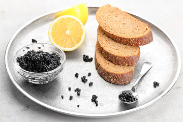 Plate with black caviar and slices of bread on table