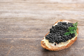 Bread with black caviar and butter on wooden table