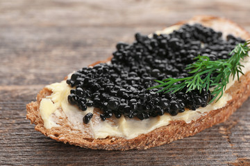 Bread with black caviar and butter on table