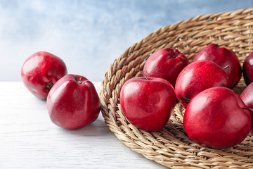 Wicker plate with ripe red apples on table