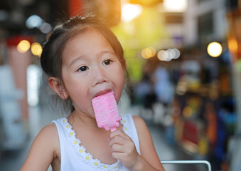 Little asian child girl eating ice-cream.