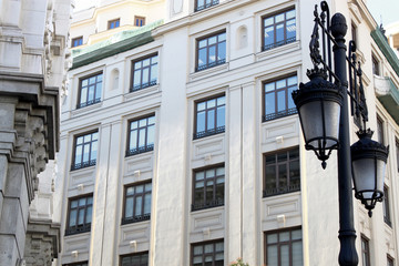 Detail of an old lamp post and facade of a historical building on the famous avenue of Gran Via in Madrid, Spain