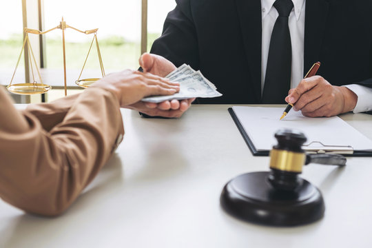 Bribery and corruption concept, bribe in the form of dollar bills, Businesswoman giving money to male lawyer while helps making deal to agreement a real estate contract and financial corporate