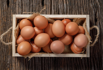 Brown eggs in wooden box on wooden table, Chicken Egg