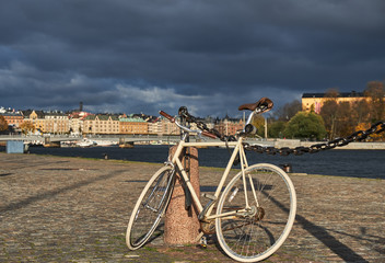 Bicycle infront of a view at the old European city. Bicycle parked near water in Stockholm, Sweden