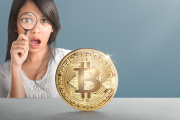 Young asian woman with magnifier looking at golden bitcoin