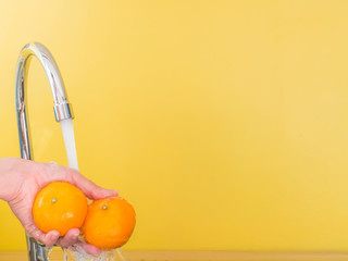 The woman are washing or rinsing her oranges eating or serving.